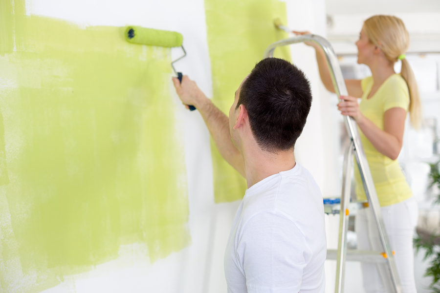 Couple in their new home painting wall in green